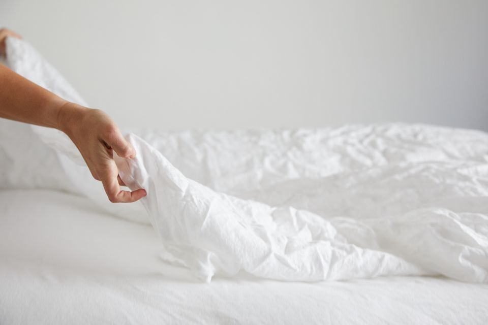 person putting sheets on a bed