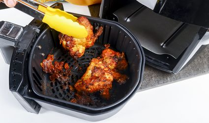 Yellow tongs removing fried chicken from air fryer
