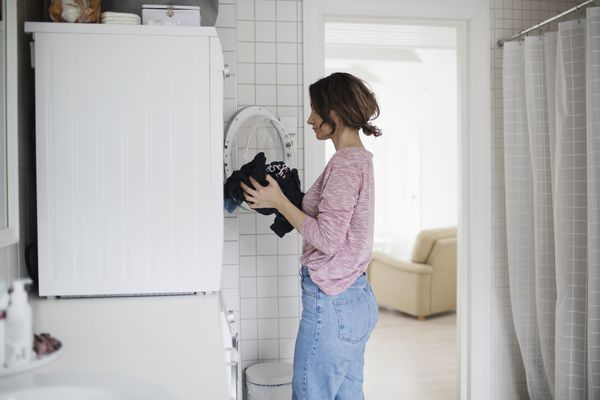 Woman putting dirty clothing into a front-loading washing machine.
