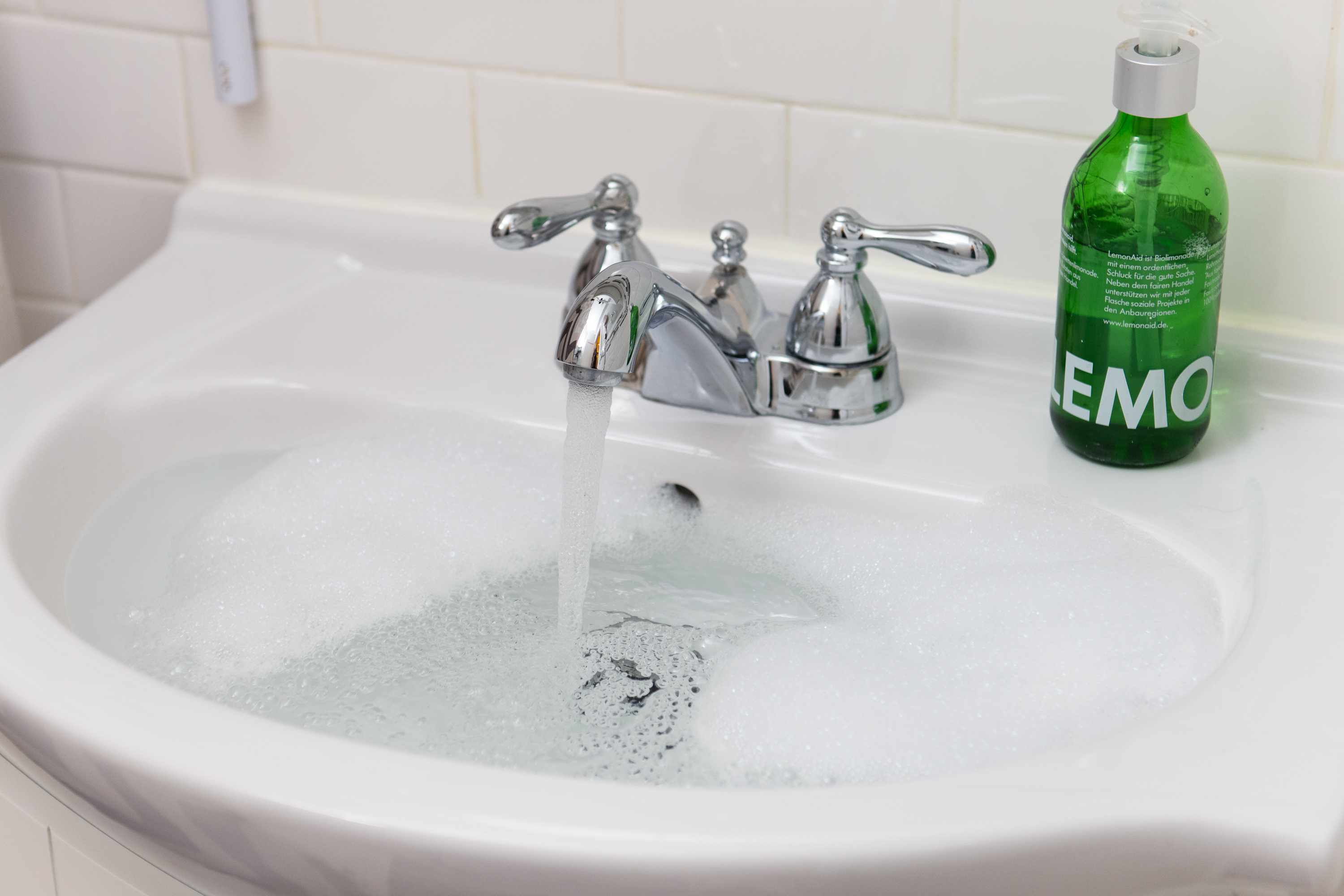 Flushing the sink with water from the tap