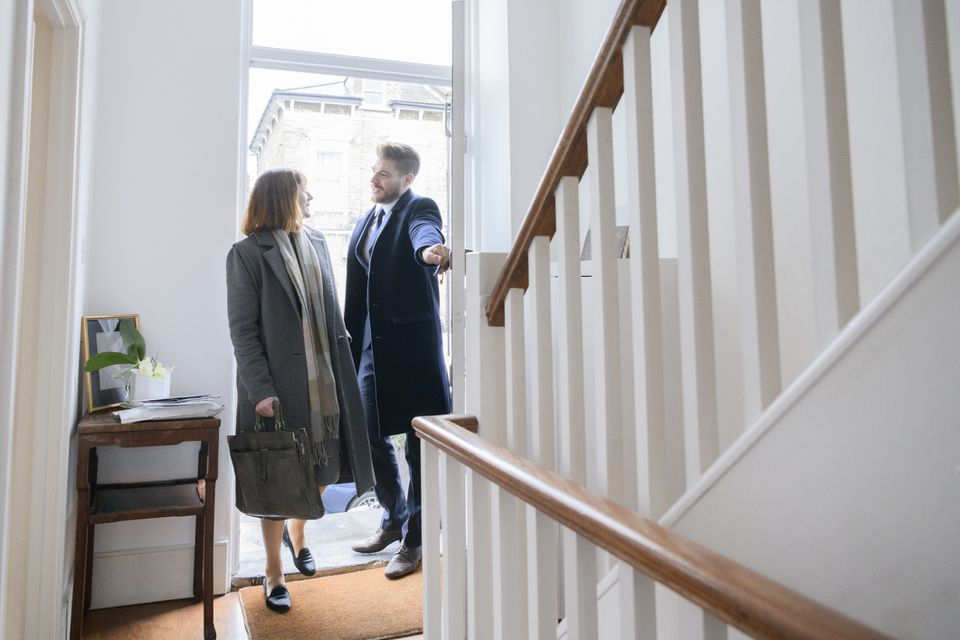 Mid adult couple arriving home after work and entering hallway