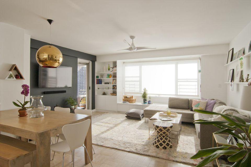 Sala y comedor en colores claros y luminosos con gran ventanal.