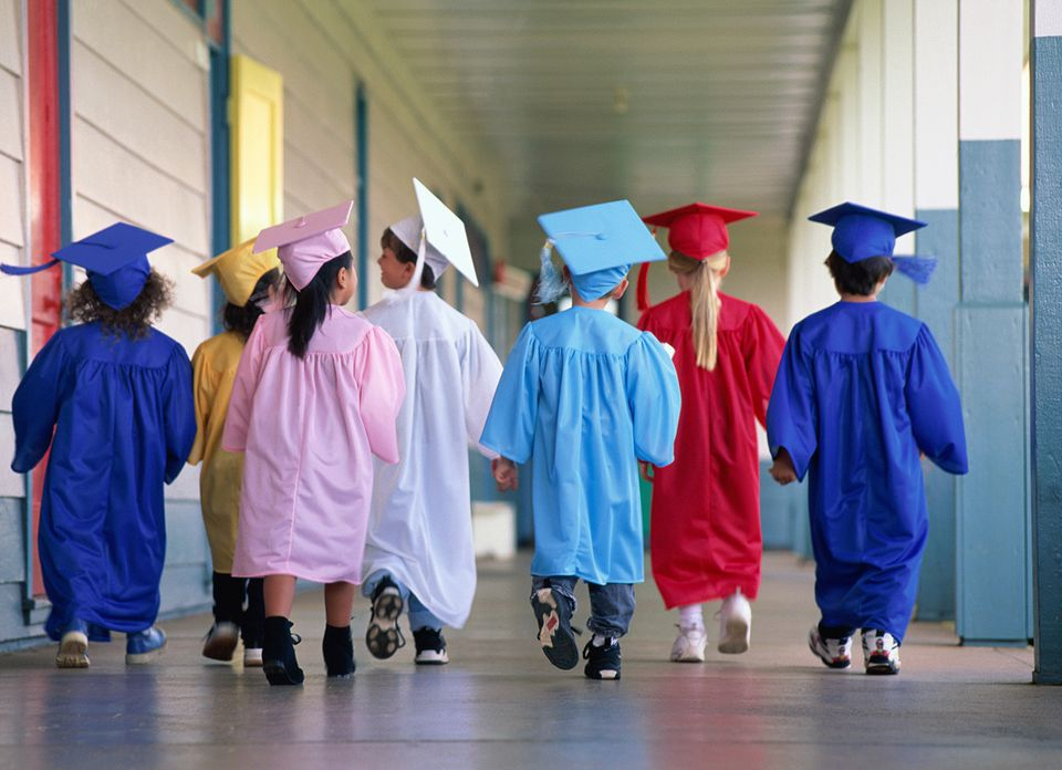 Group of children wearing graduation robes, rear view