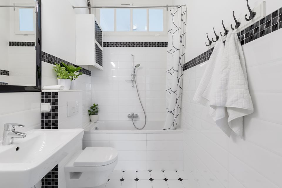 Towels and mirror in white and black bathroom with bathtub and toilet. Real photo