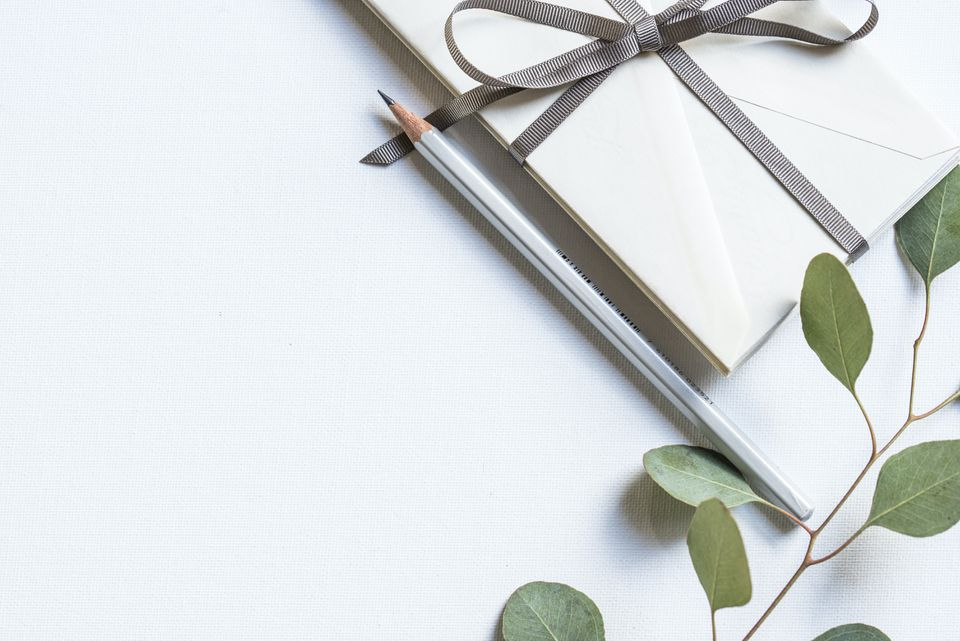 Envelope by pencil and plant branch