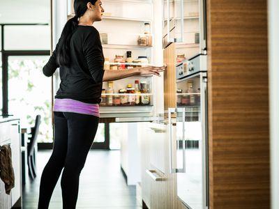 A woman opening a counter-depth fridge