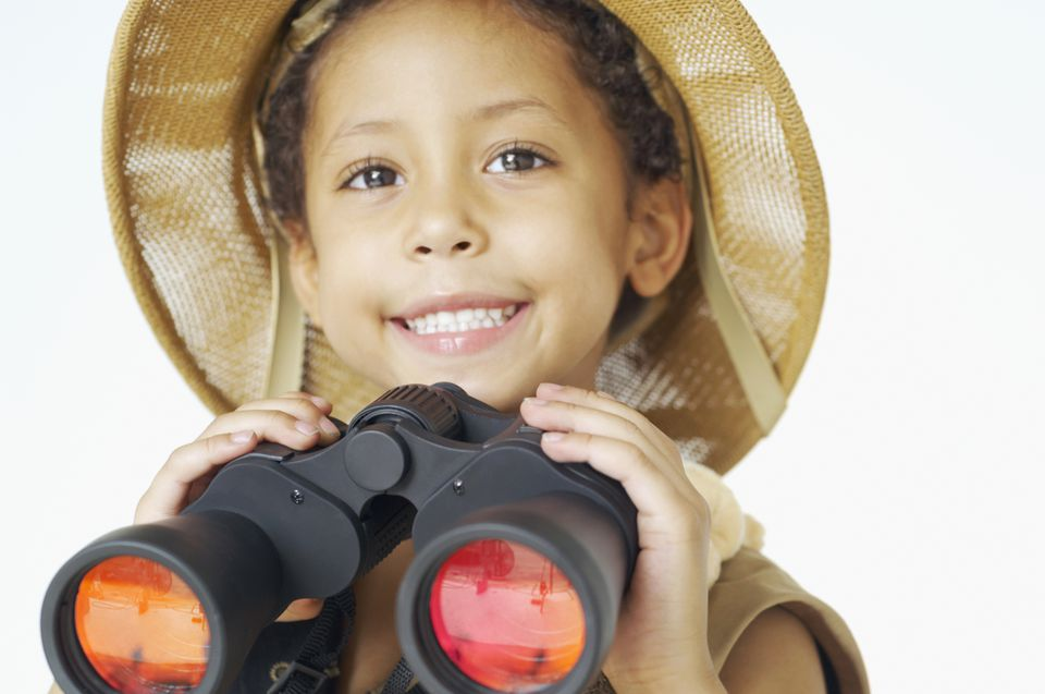 Mixed race boy in safari hat holding binoculars