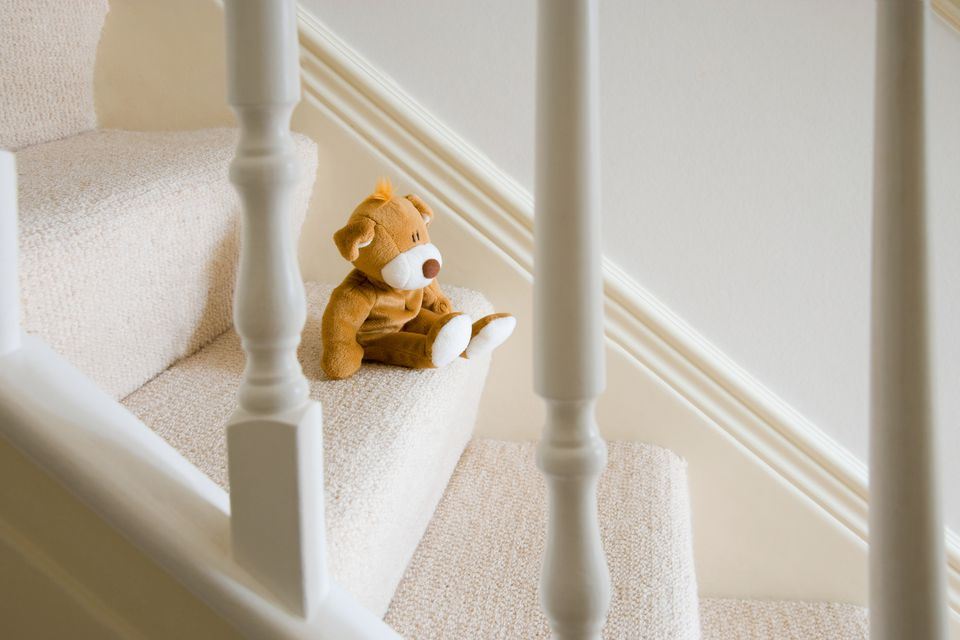 Stuffed bear on carpeted stairs.