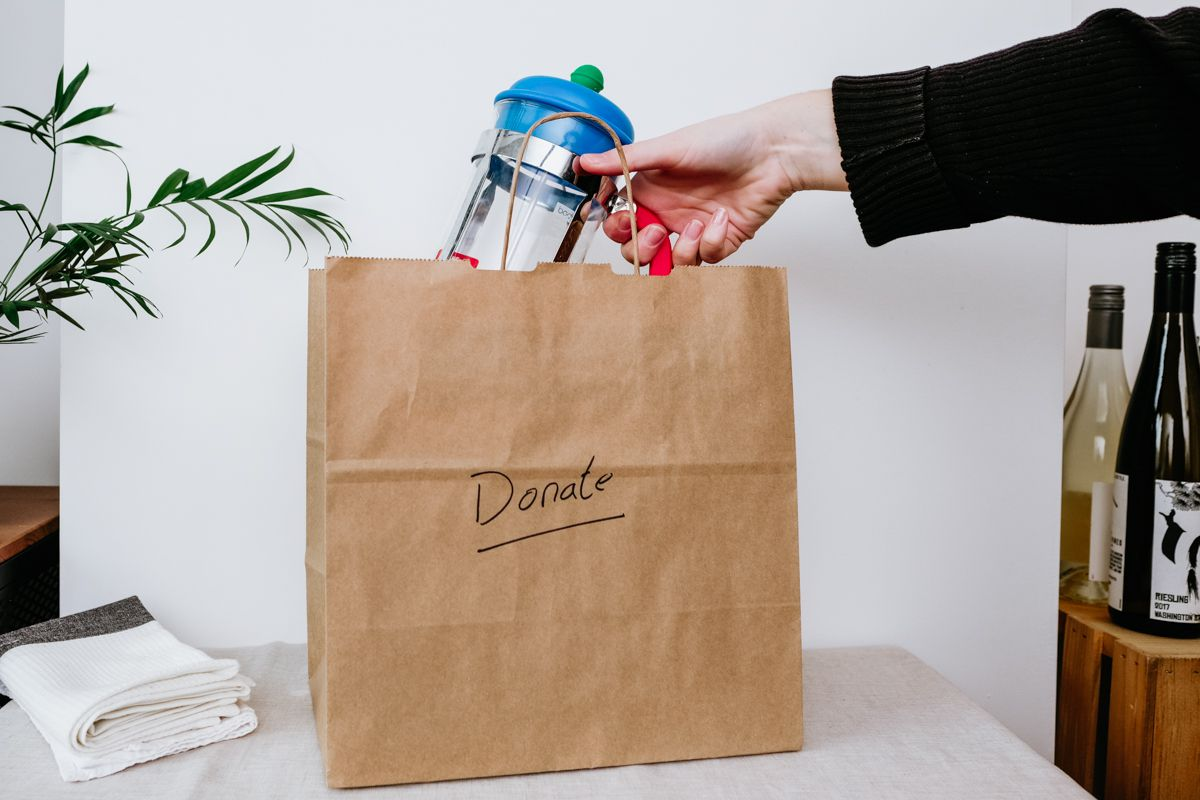 woman putting items in a donation bag