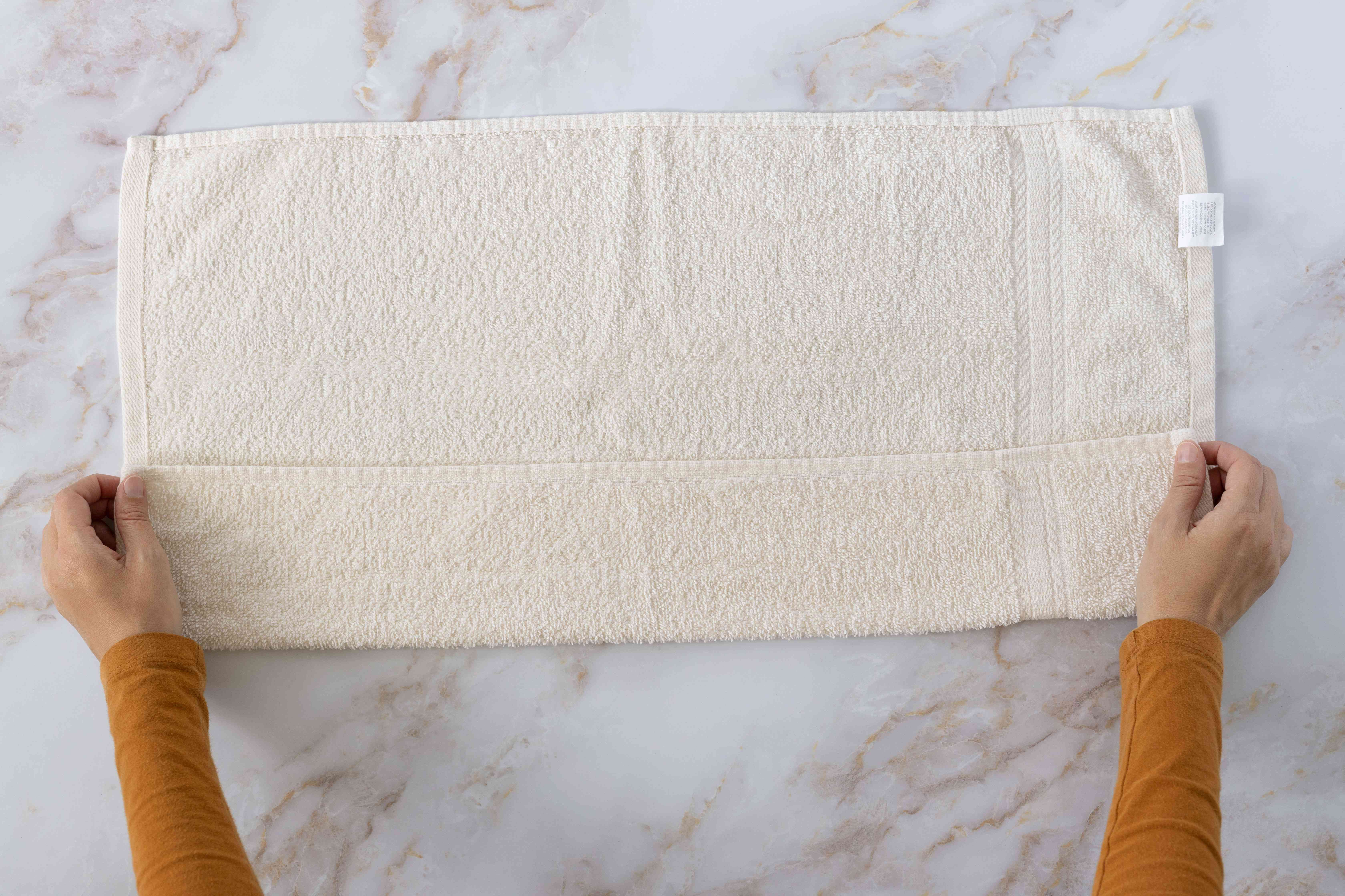 Cream towel folded longwise to the center and held by corners