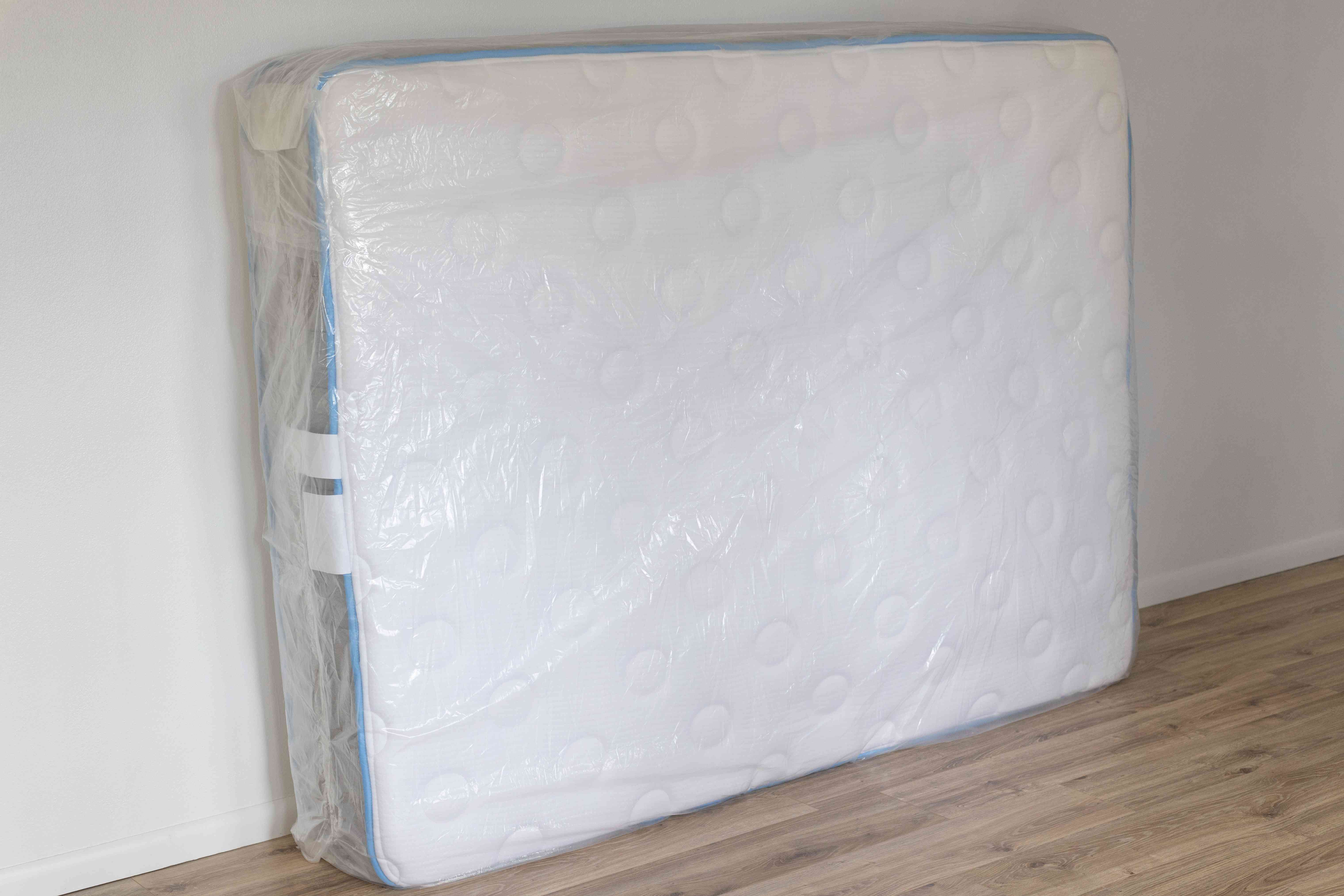 Mattress in clear mattress bag stacked on its side and leaning on wall