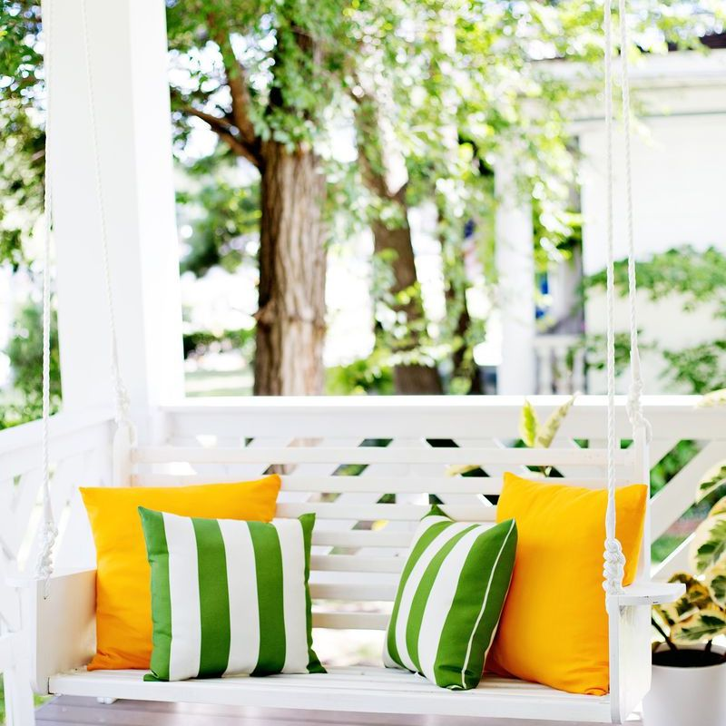 A white porch swing with colorful pillows