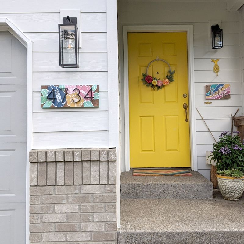Colorful painted address sign on a house exterior.