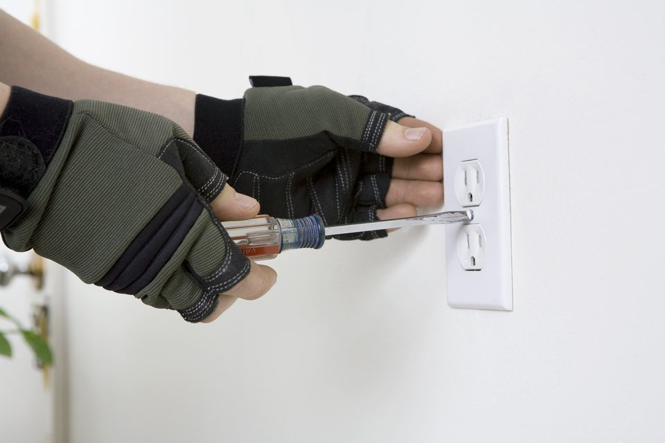 Male hands screwing in electical outlet