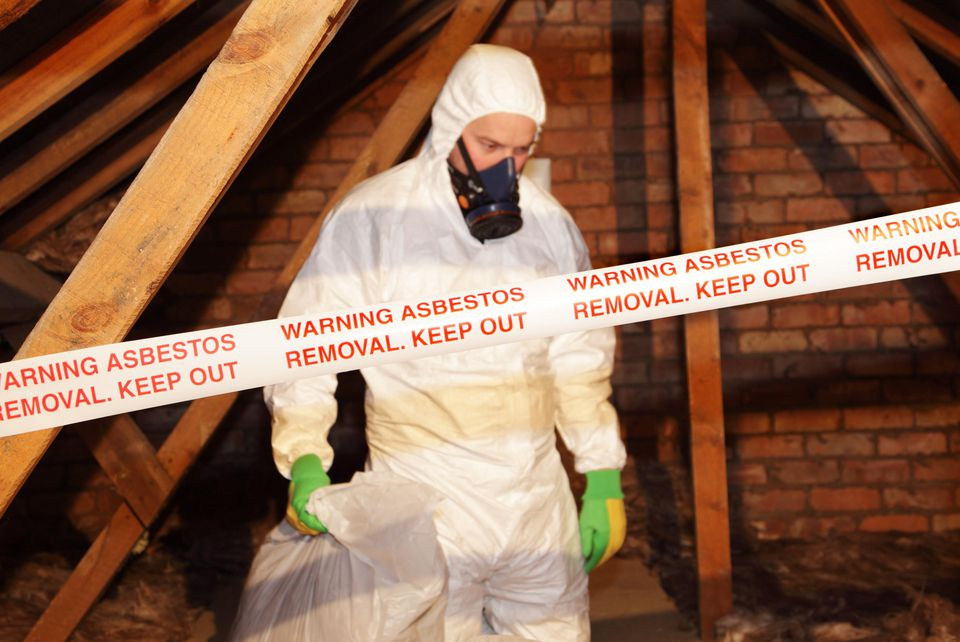 Man removing asbestos from an attic