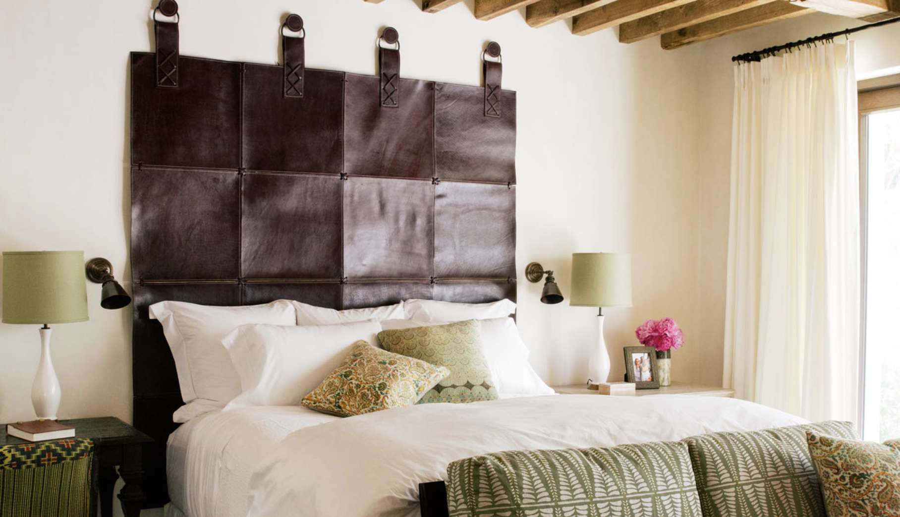 earthy style mediterranean with exposed wooden beams, green colored fabrics, leather headboard