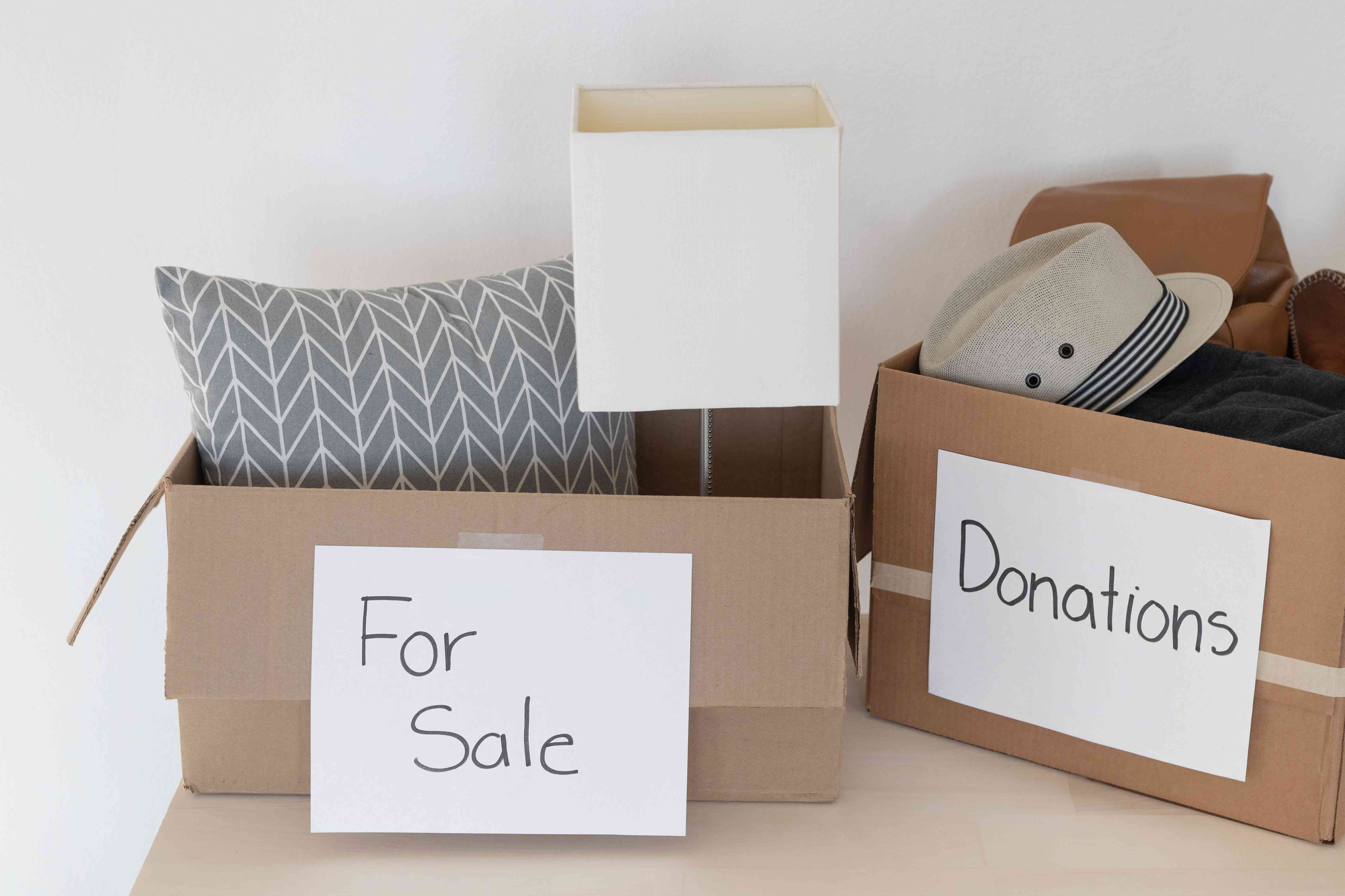 Moving boxes labeled for sale and donations with items inside