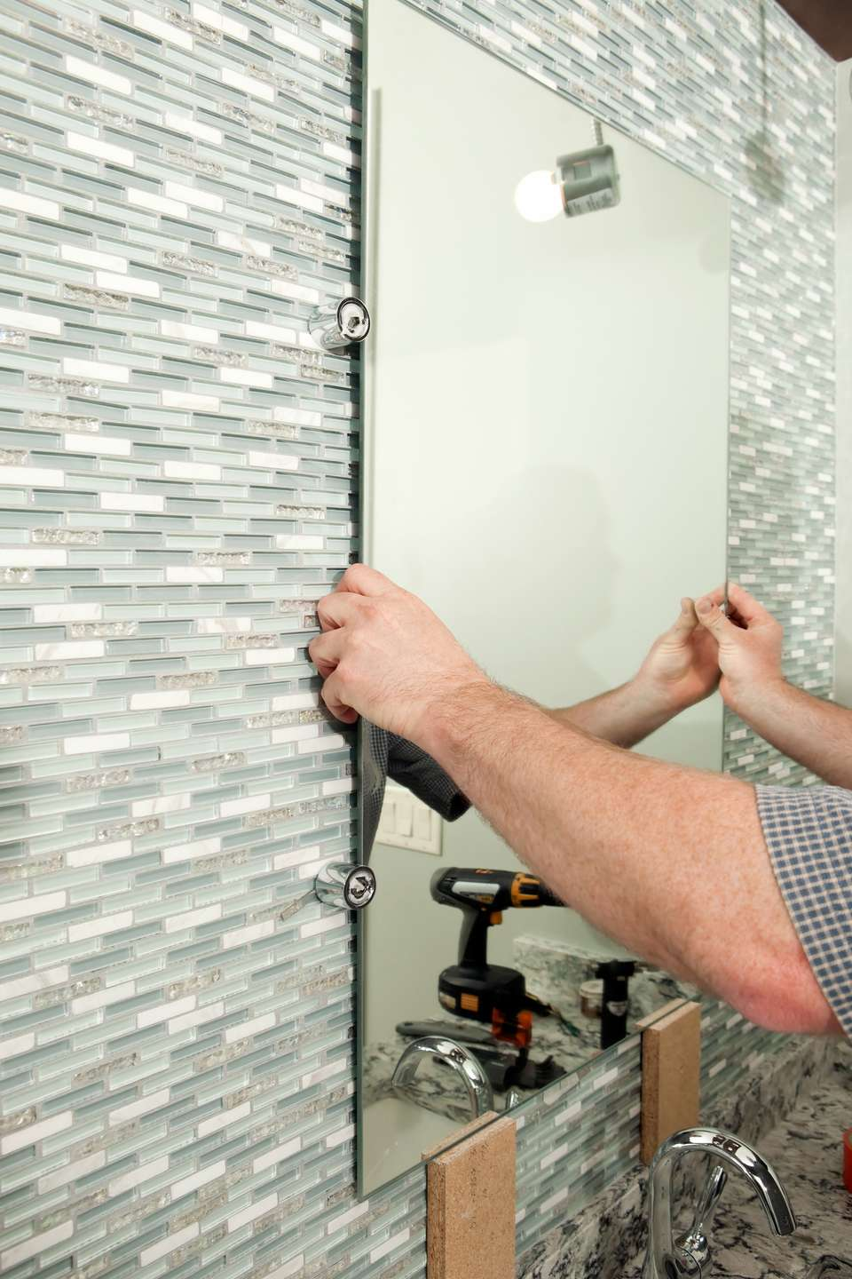 Worker installing a new bathroom mirror against a tile backsplash.