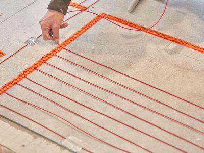Radiant heat flooring system orange wires being installed on ground