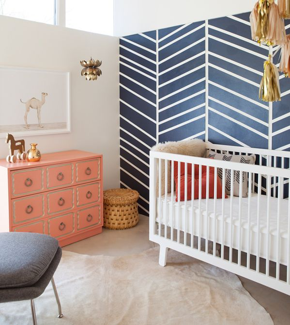 A neutral nursery with stunning navy focus wall and trendy gold and coral accents.