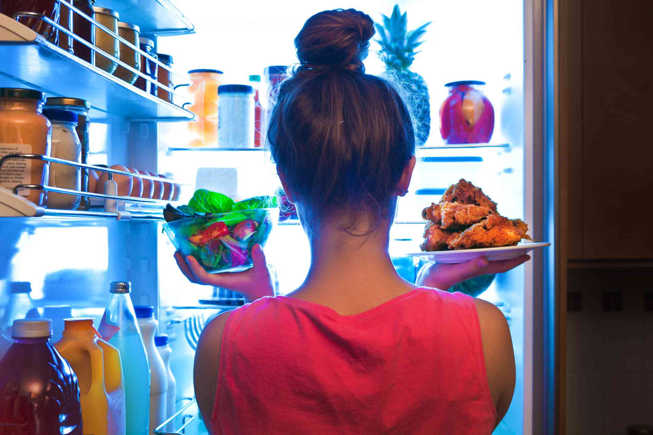 Woman pulling unwrapped food from the fridge.