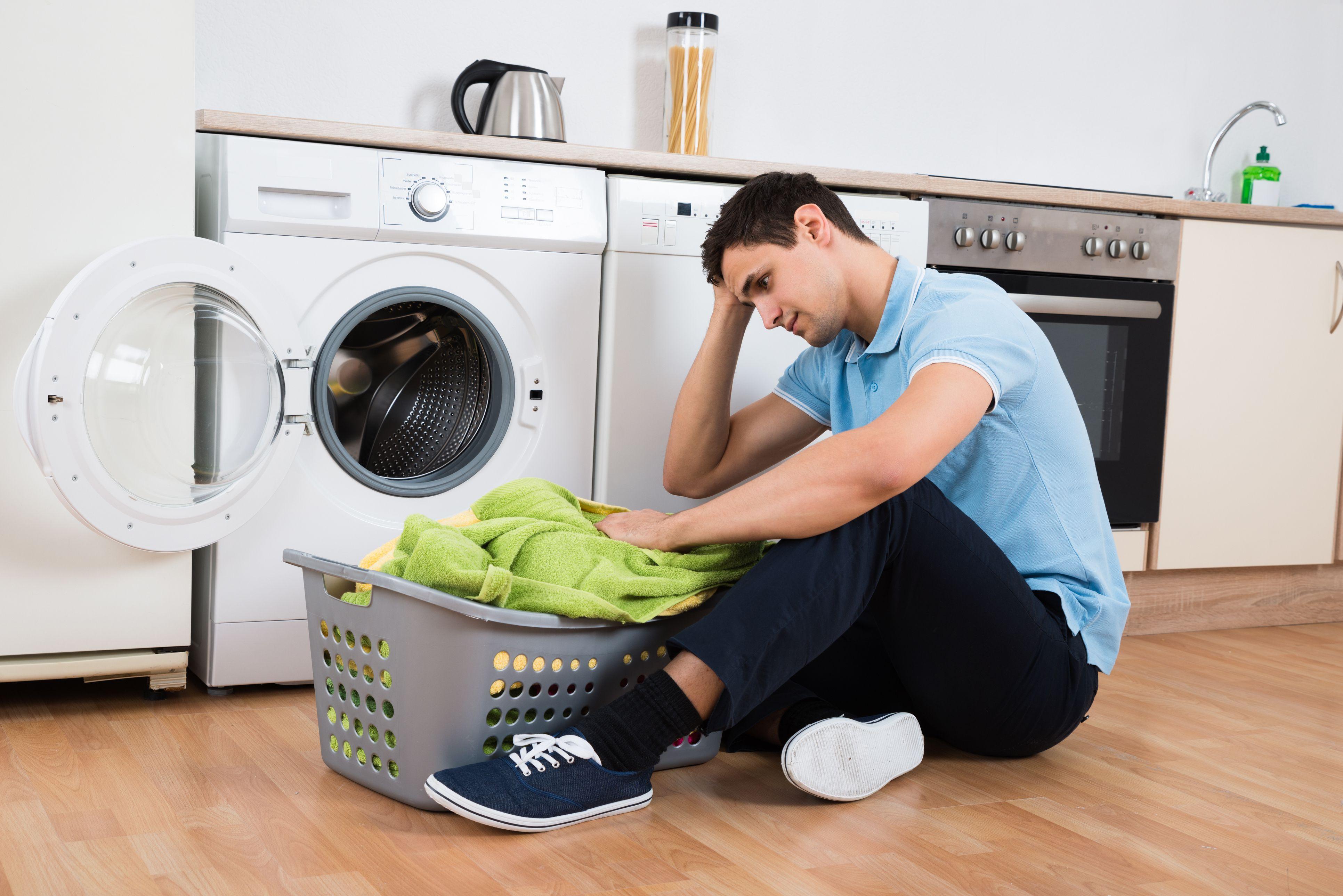 Tensed man looking at laundry basket by washing machine