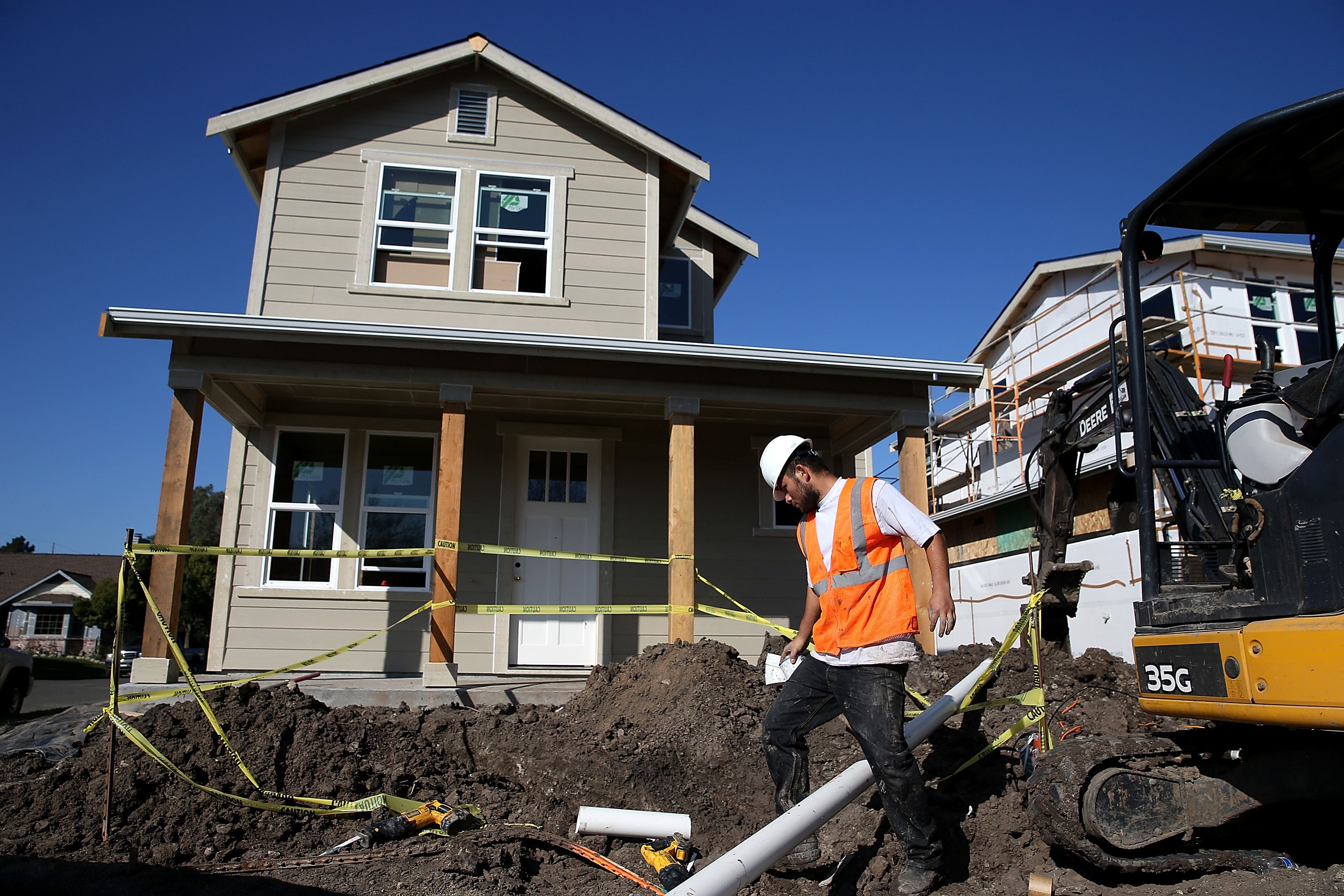 A worker prepares to move a piece of pipe into place as he builds a new home on January 21, 2015 in Petaluma, California.