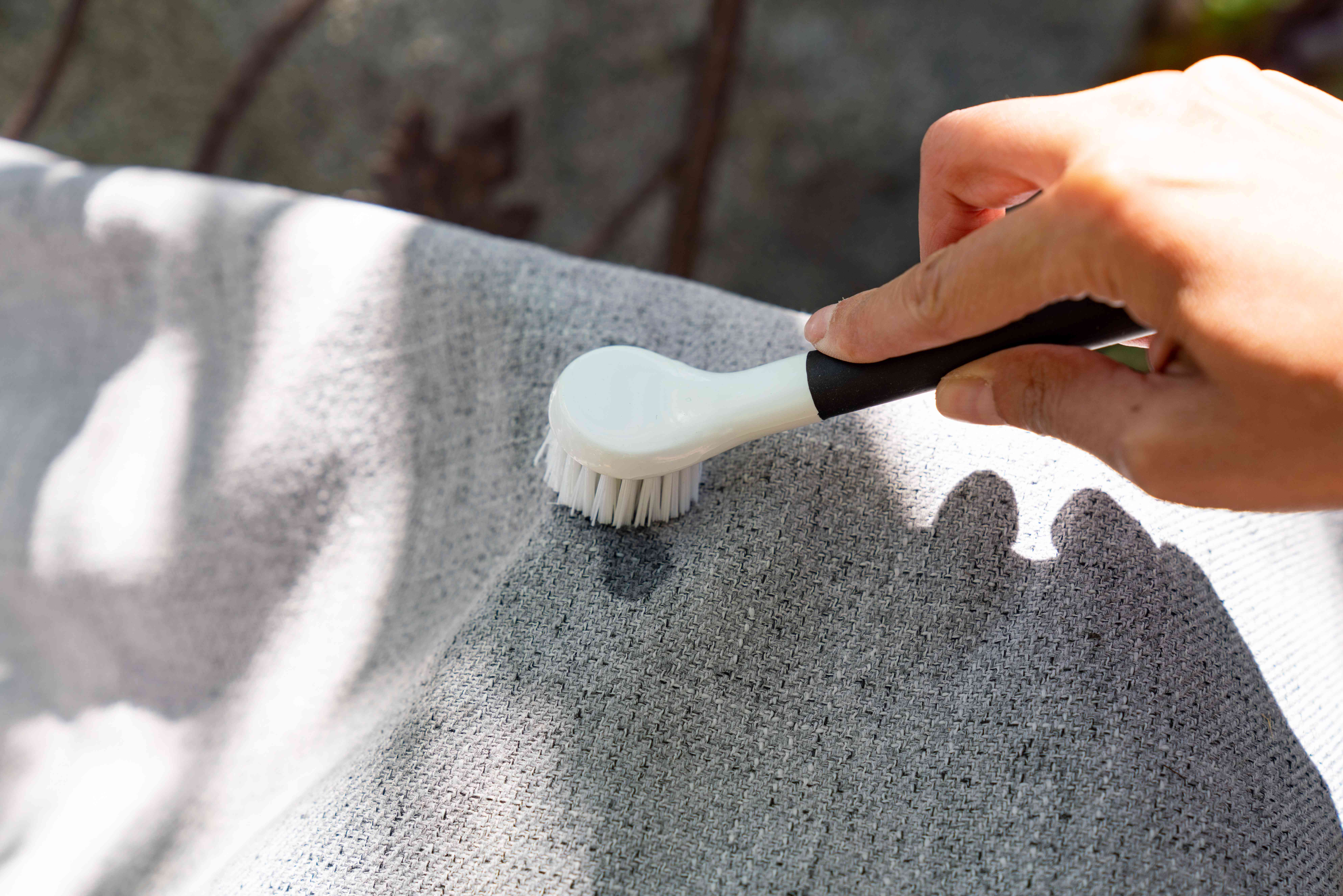 Heavy duty laundry detergent scrubbed into outdoor fabric furniture with soft-bristled brush