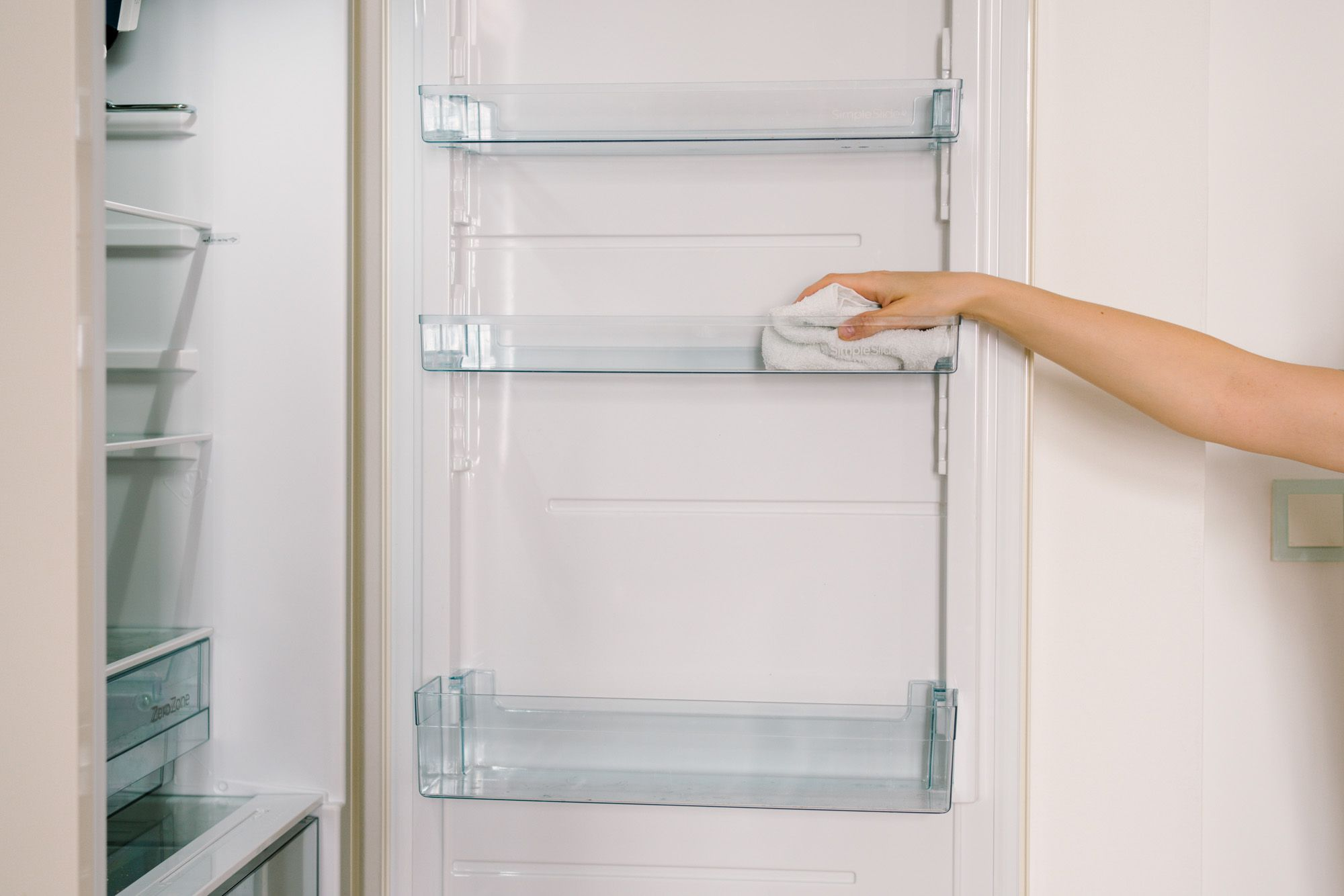 person wiping down refrigerator shelves
