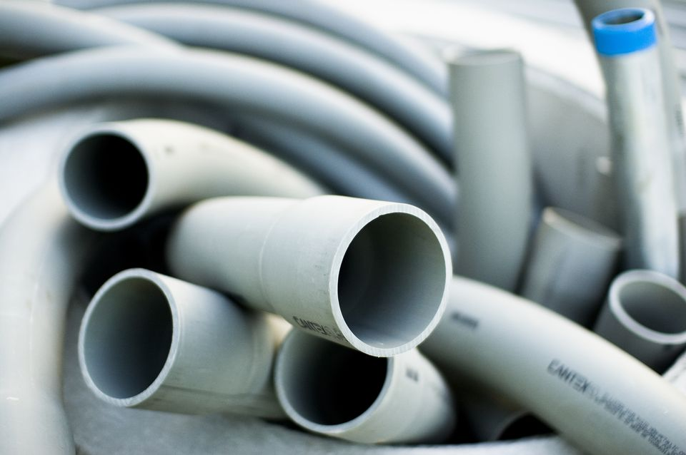 Collection of grey PVC plastic tubing for use as a conduit for electric wires.