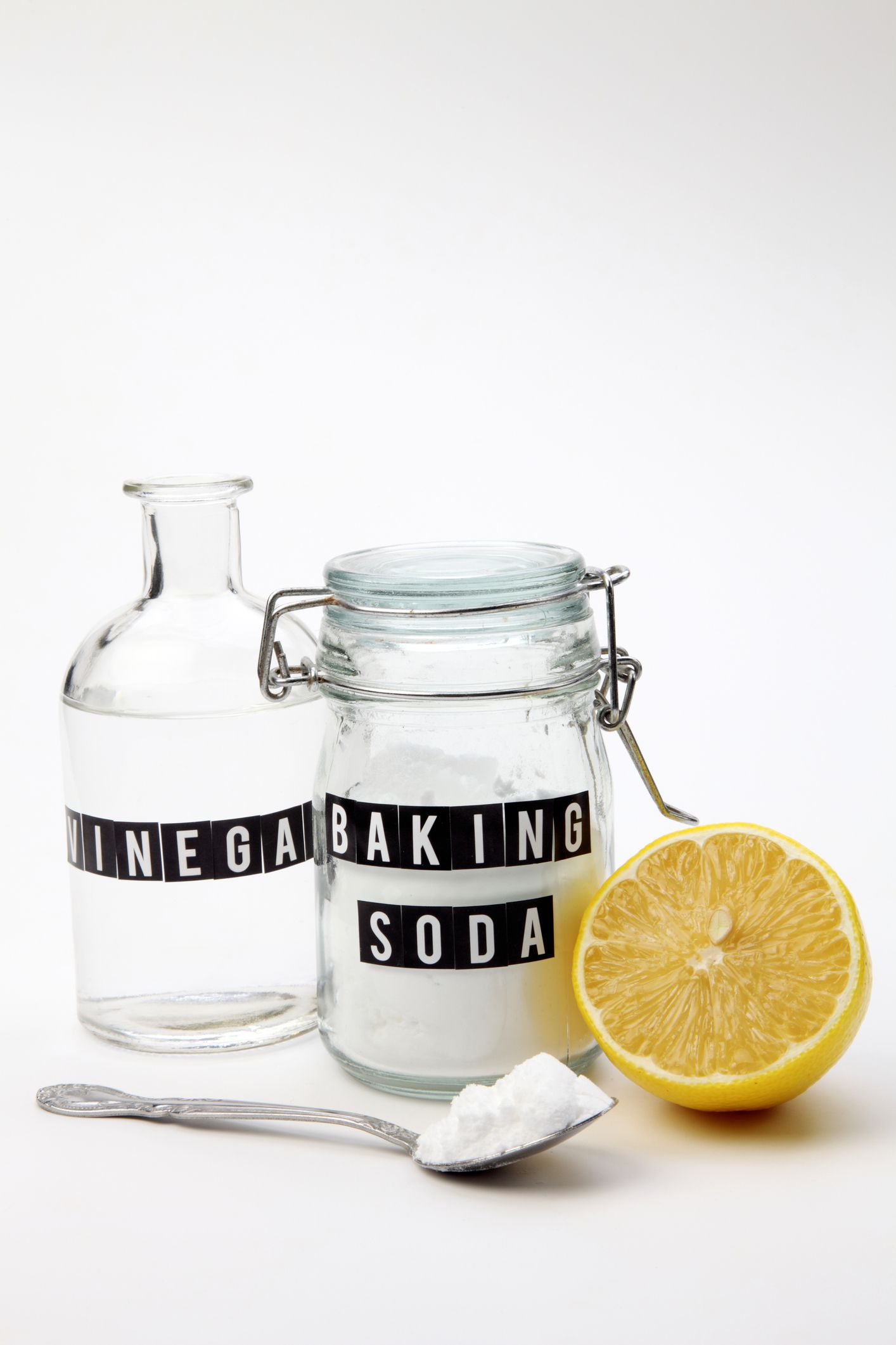Vinegar and baking soda next to a lemon