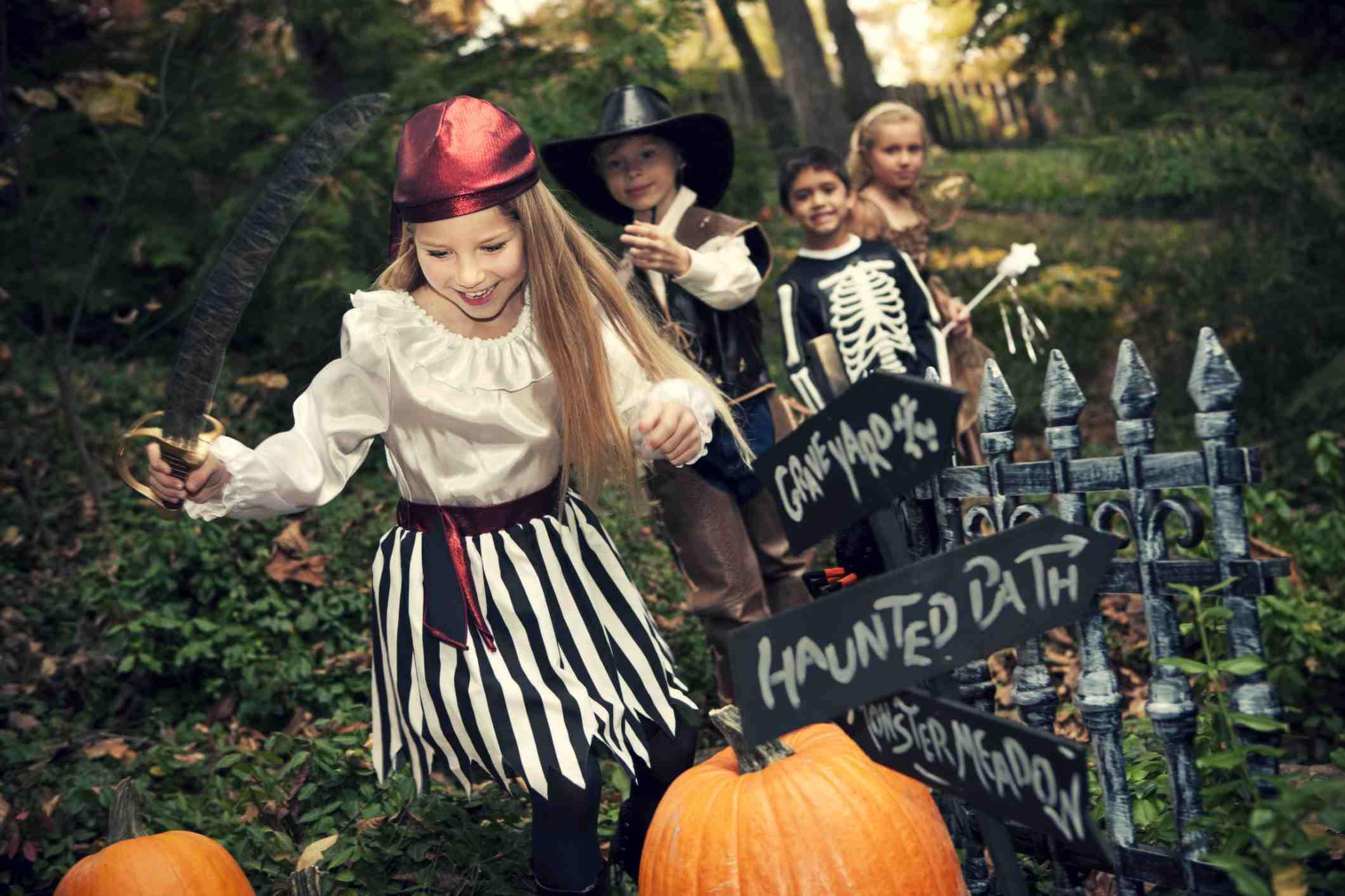 Un grupo de niños corriendo en sus disfraces de Halloween