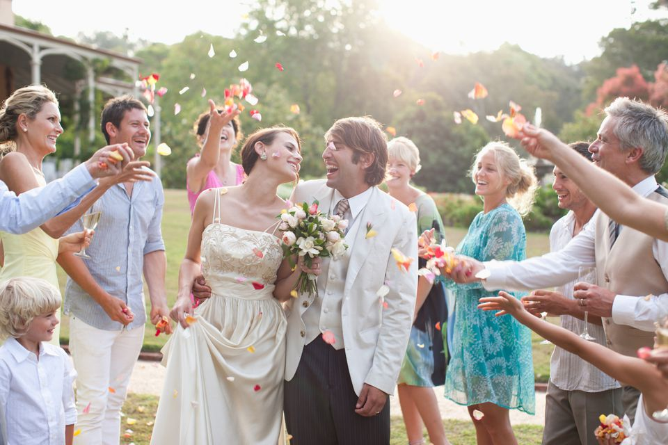 Guests throwing petals over bride and groom