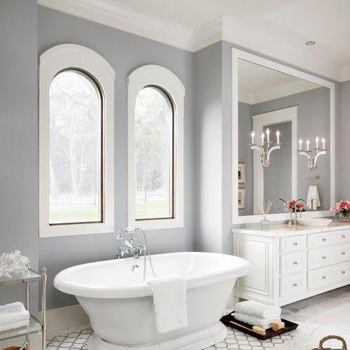Gray, white bathroom with freestanding pedestal tub
