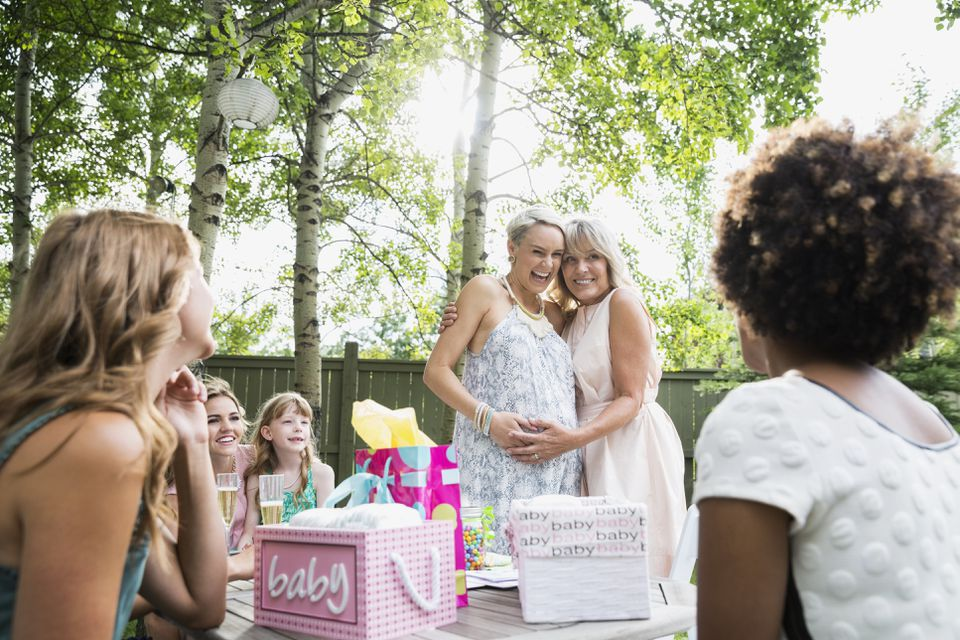 Mother and pregnant daughter hugging backyard baby shower