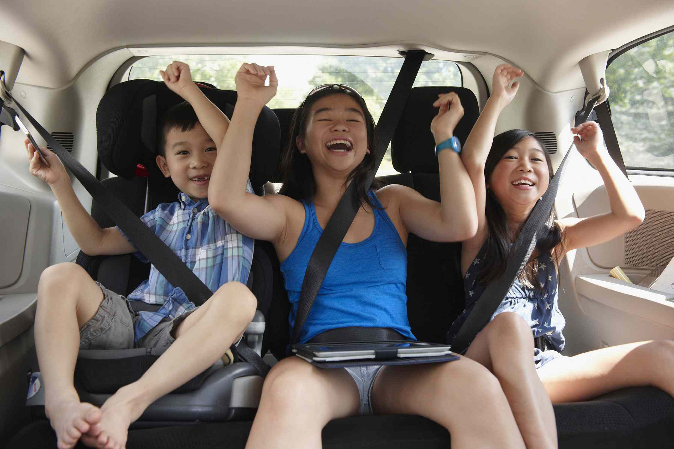 excited kids in the backseat of a car