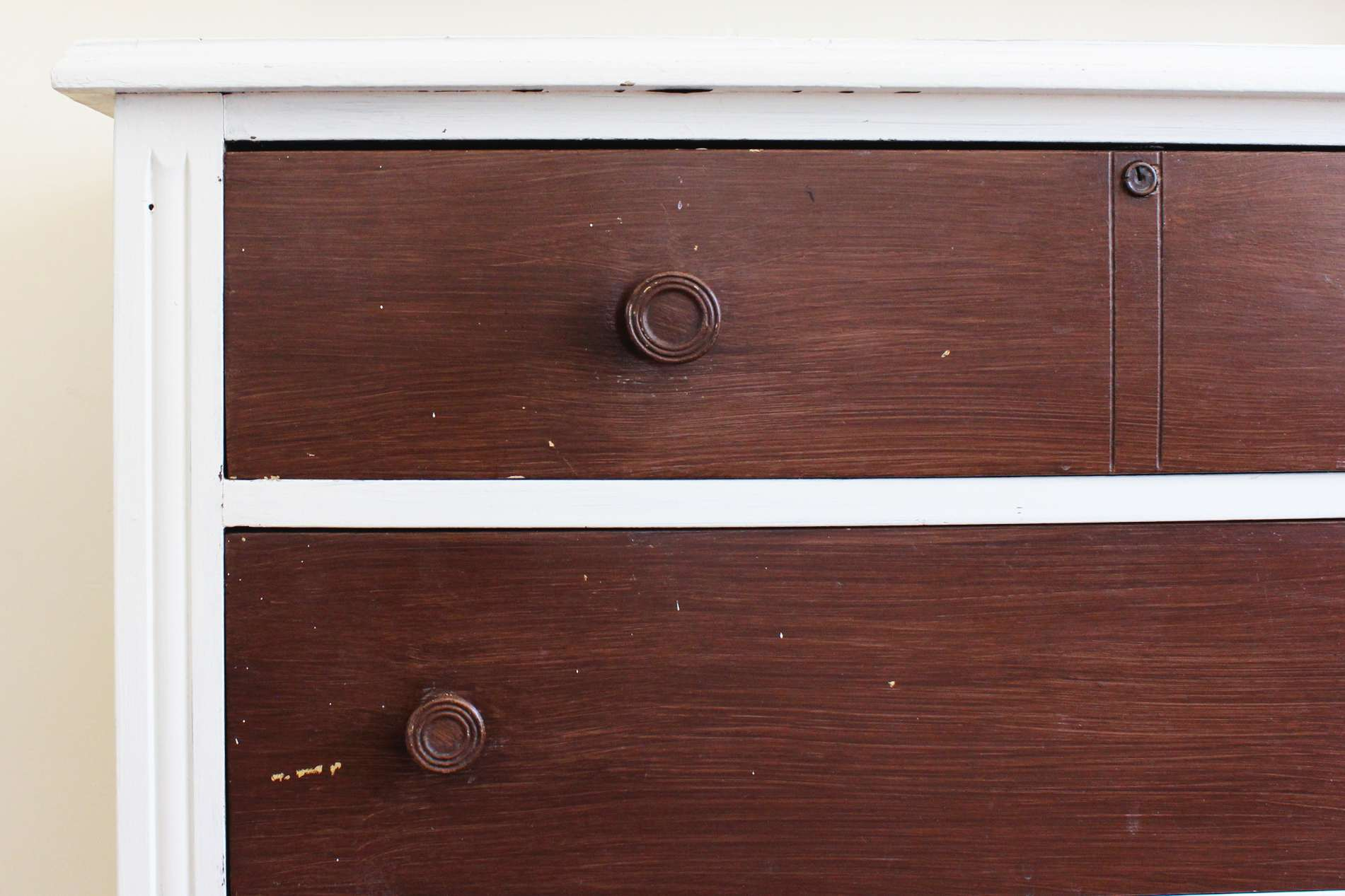 A Picture Of An Old Wooden Dresser With White Trim