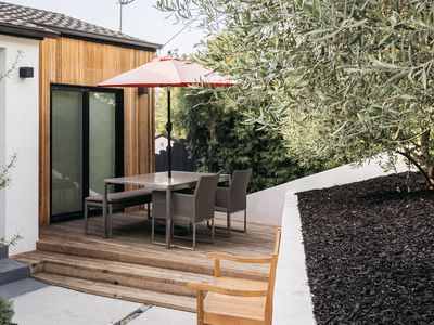 Outdoor deck with umbrella covering outdoor seating and table