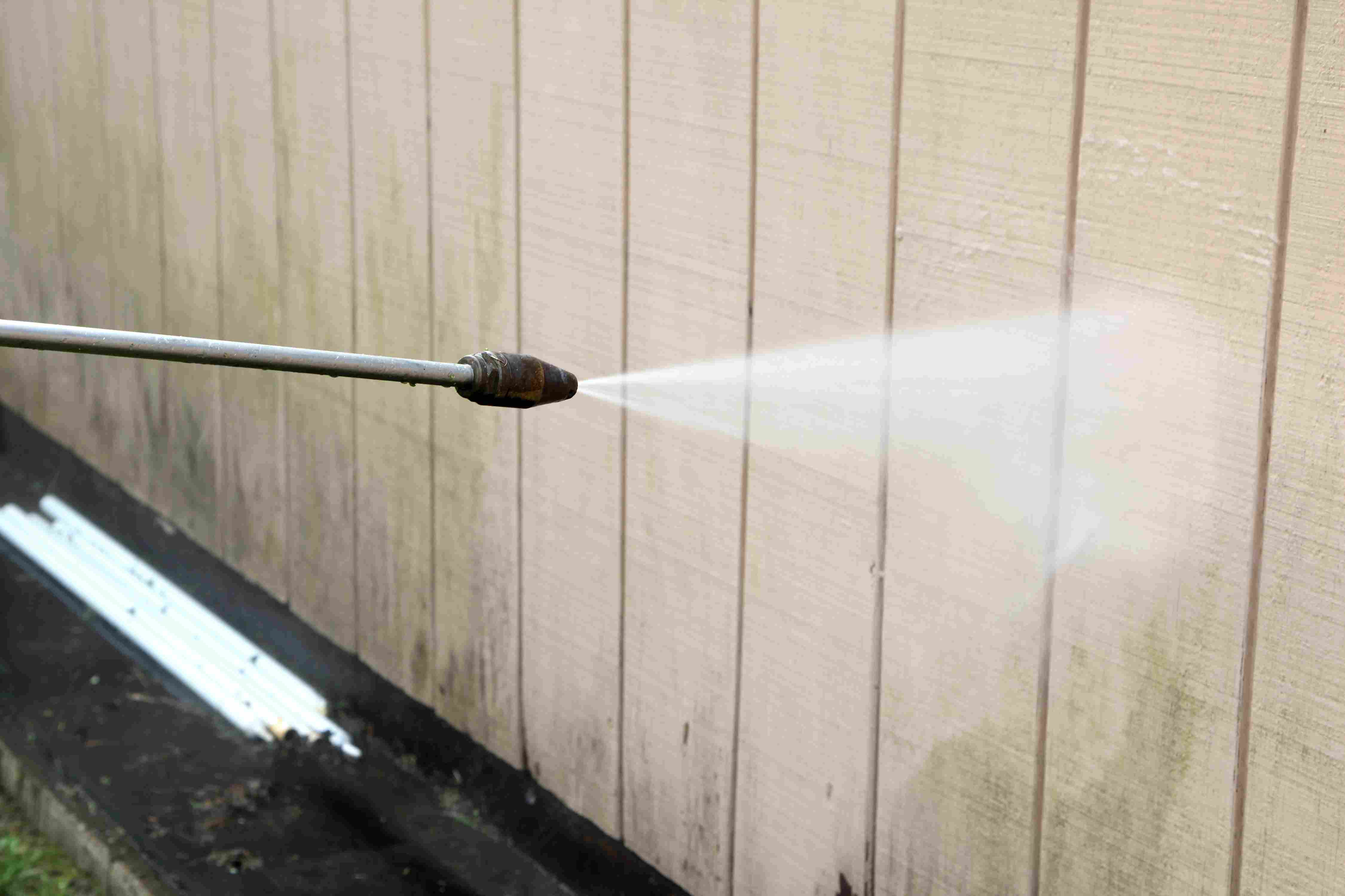 Power-washer spraying a wood wall