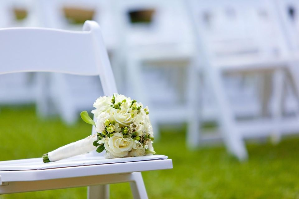 A pearl bouquet at an outdoor field with white chairs