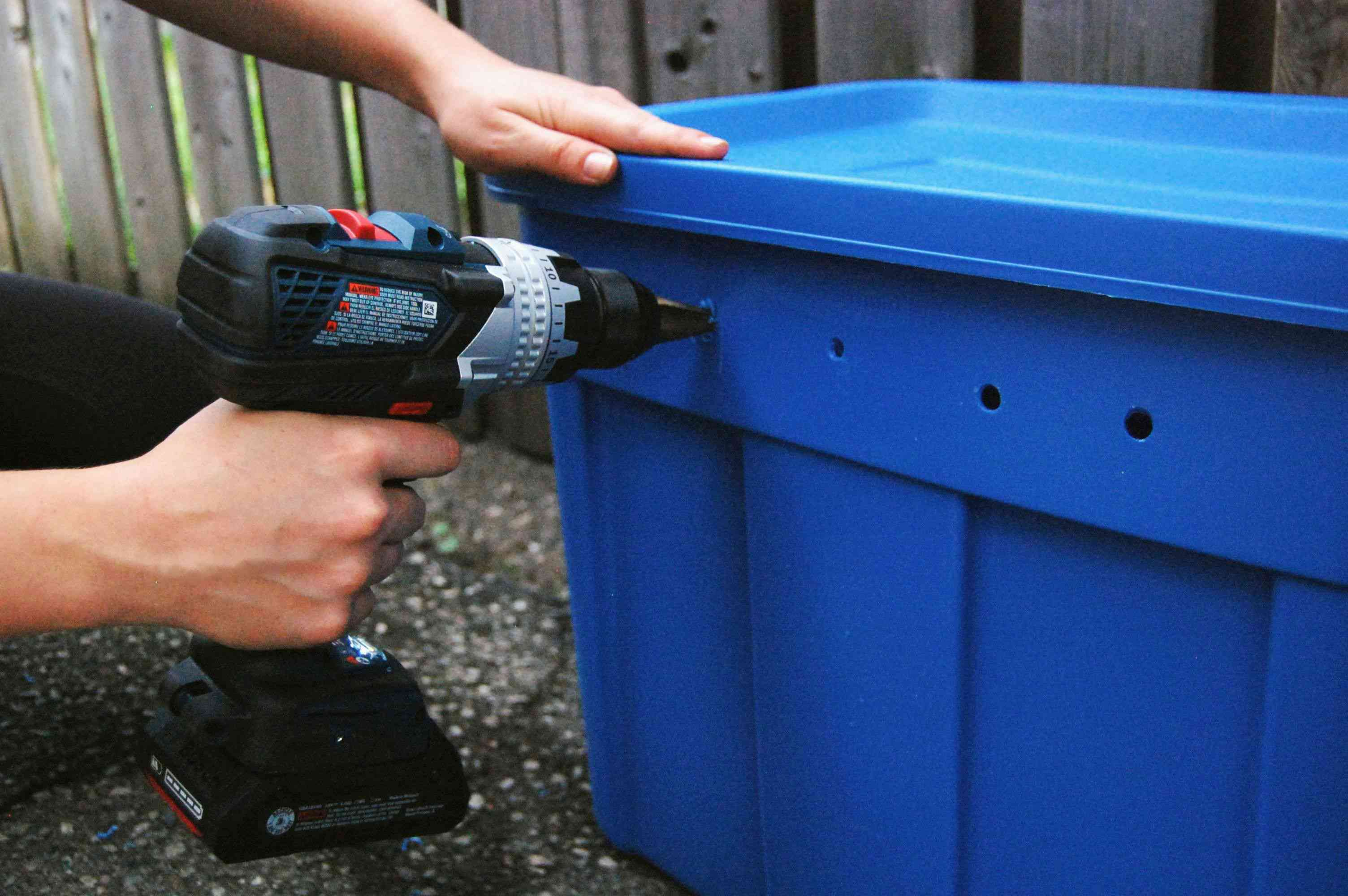 Drilling holes in the sides of the bin