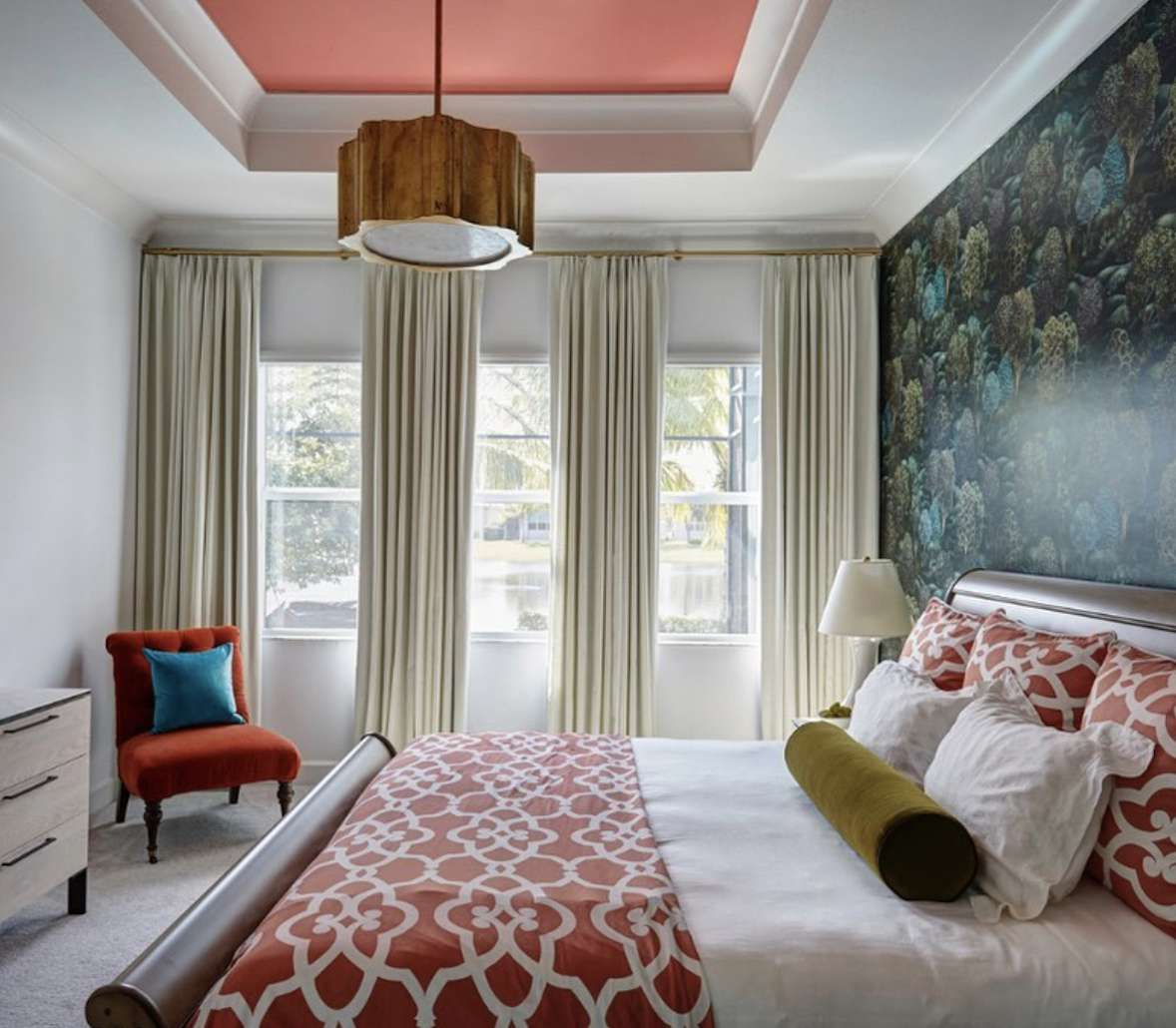 bedroom with blue and green wallpaper, red patten bedspread and pillows, red chair with solid blue pillow in corner