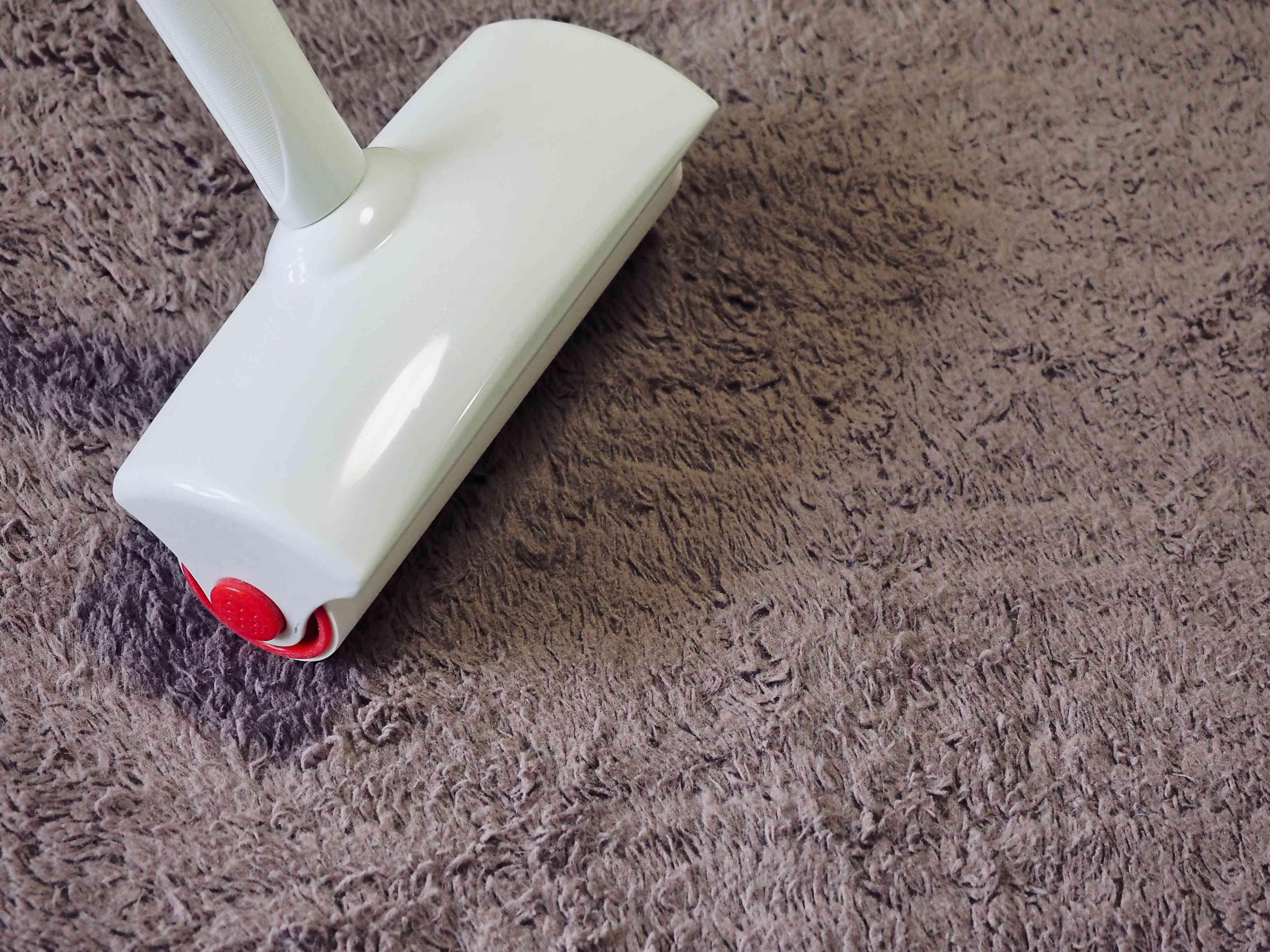 White floor sticky roller on gray carpet
