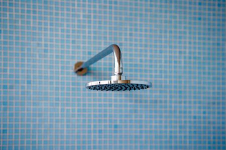 Close Up Of Shower Head Against Blue Tiles