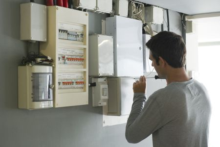 man opening fuse box, rear view