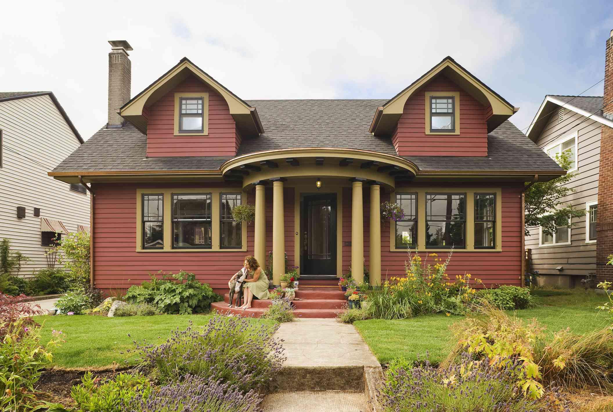 Mujer y perro sentados en el porche de una pintoresca casa