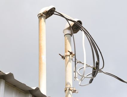 Power mast with weather-head protecting electrical service line