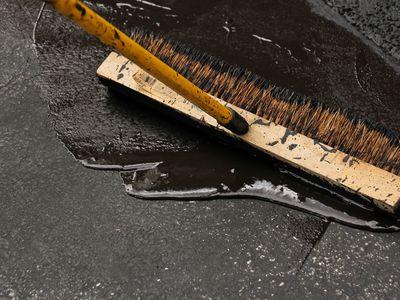 A broom and tar used to seal asphalt driveways