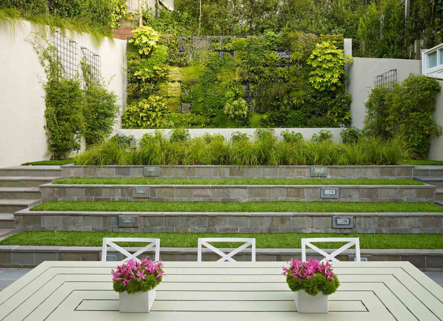 Vertical garden with vines climbing on walls along with a white table, chairs, and flowerpots with pink flowers.