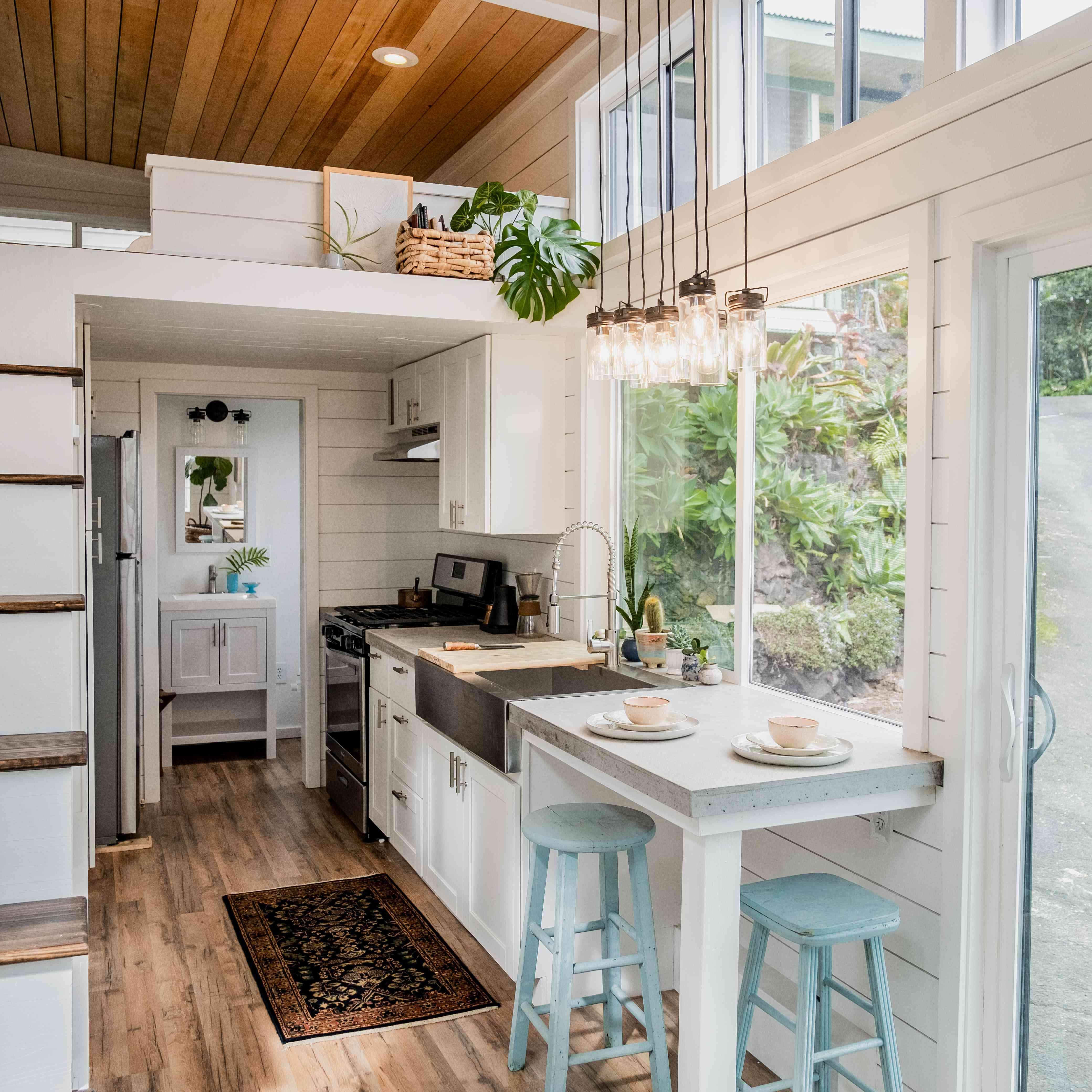 airy tiny home kitchen with white cabinets